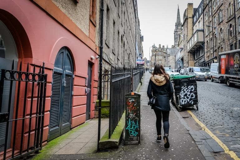 woman walking down the cobbled streets enjoying her time in edinburgh, scotland